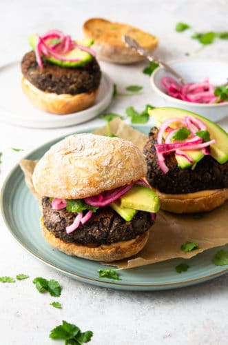 A photo of a quinoa veggie burger on a plate with pickled onions, and avocado.