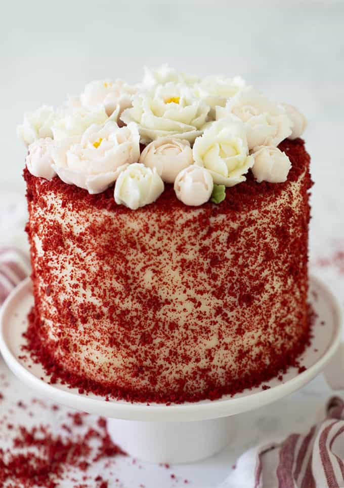 A red velvet cake covered in red crumbs and topped with buttercream roses.