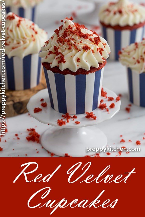 A clipping of a red velvet cupcake on a cupcake stand with red velvet crumbles on top.