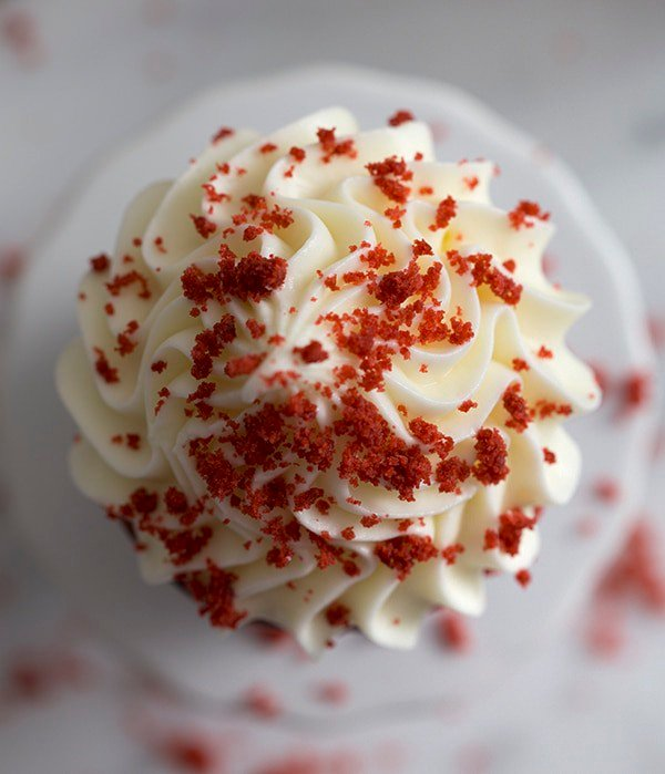 A top down photo of a red velvet cupcake with red crumbs on top the frosting.