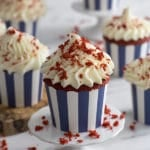 A close up photo of a red velvet cupcake sprinkled with crumbs on top of the frosting.