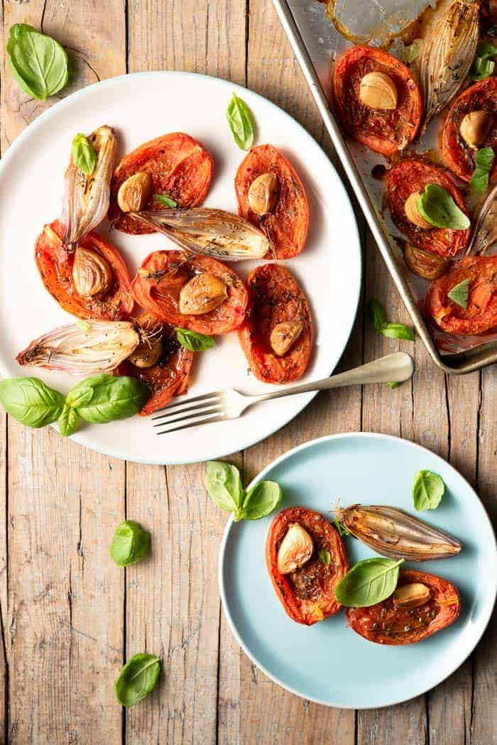 An overhead shot of two plates of oven roasted tomatoes, shallots and basil sitting on a rustic wooden surface