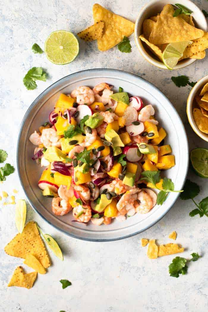 An overhead shot of shrimp ceviche in a blue blow with lime wedges and tortilla chips