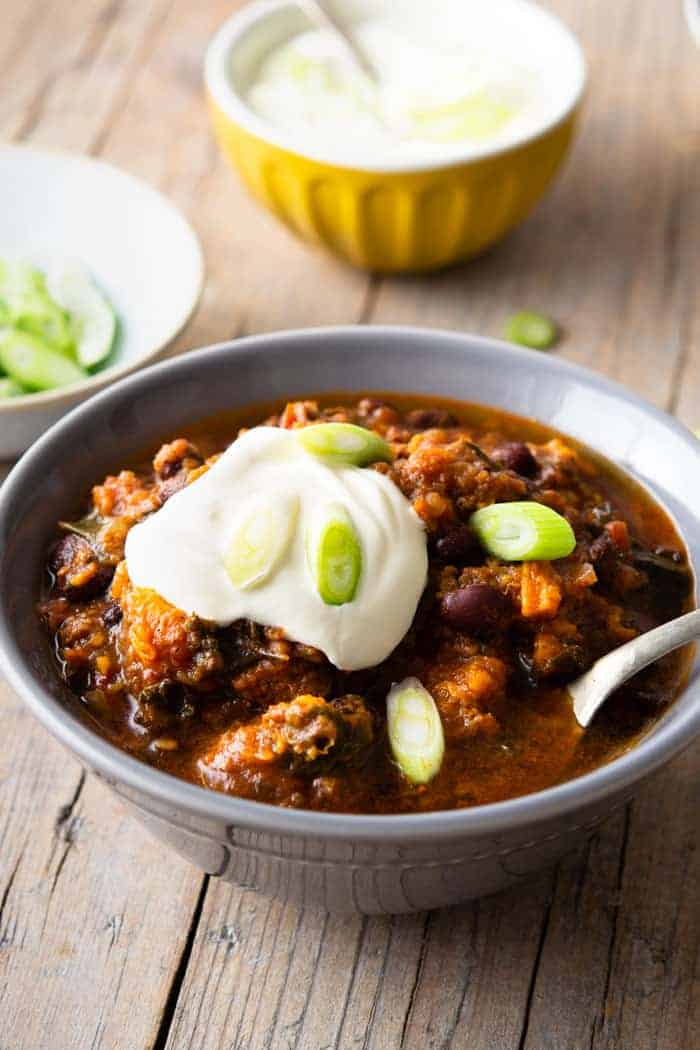 A gray bowl filled with slow cooker chili and topped with sour cream and sliced scallions