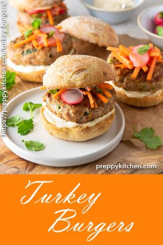 A clipping of two turkey burgers on a plate with smokey mayo and spicy carrot-radish slaw.