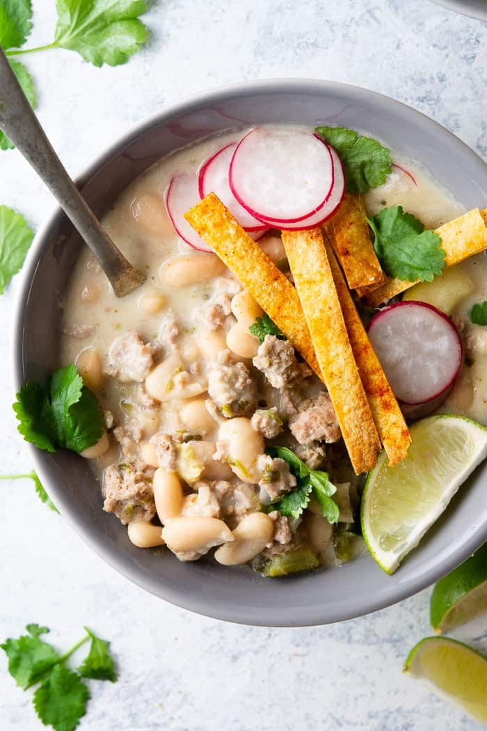 A bowl of turkey chili verde topped with fresh cilantro, sliced radishes, crunchy tortilla chips and a lime wedge.