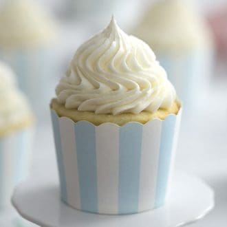 A photo of a vanilla cupcake with vanilla buttercream frosting beautifully piped on top.