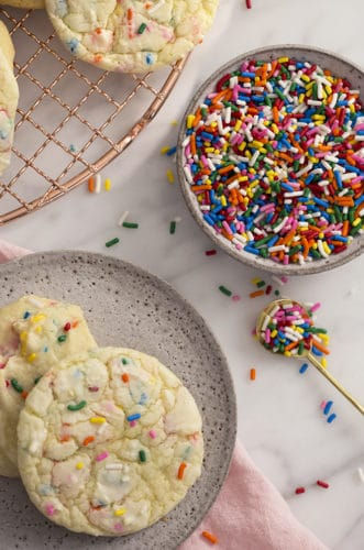 A photo showing cake mix cookies on a marble table with a bowl of sprinkles