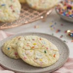 A photo od cake mix cookies that have sprinkles in them on a white marble table.