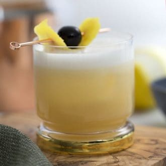 A photo of a whiskey sour in a gold-rimmed glass on an olive wood board
