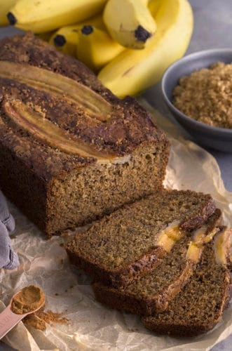 A photo showing a loaf of banana bread. Two sliced bananas have been baked into the top.