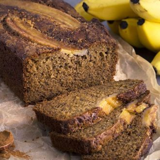 A closeup photo of banana bread with three slices cut in the foreground