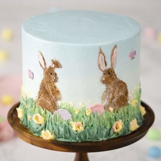 An easter bunny cake on a cake stand featuring hand painted bunnies