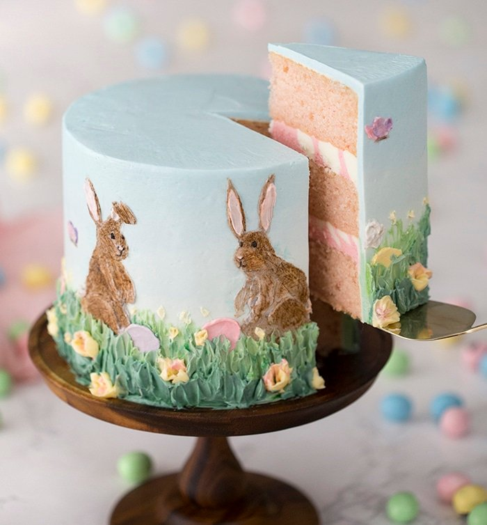A photo of an Easter cake with a piece being removed.