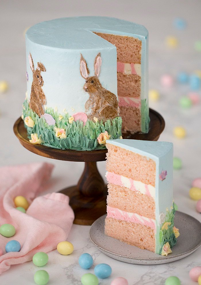 a photo showing two Easter bunnies painted in buttercream on a cake.