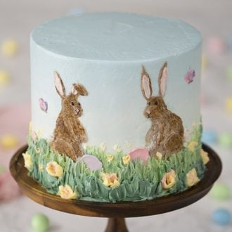 A photo of a cake with two buttercream bunnies painted on the front