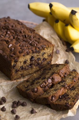 A photo showing a loaf of Chocolate chip banana bread with three slices cut out in the foreground.