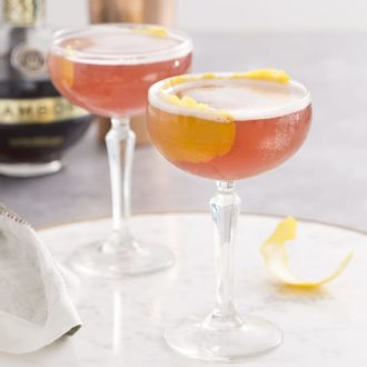 A photo showing two french martinis in coupe glasses garnished with lemon peel.