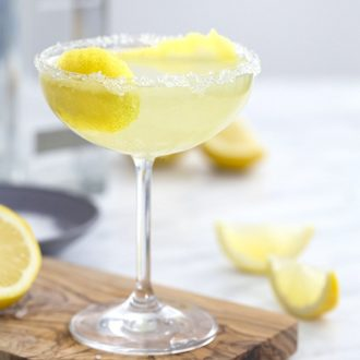 A photo of a lemon drop cocktail in a coupe glass