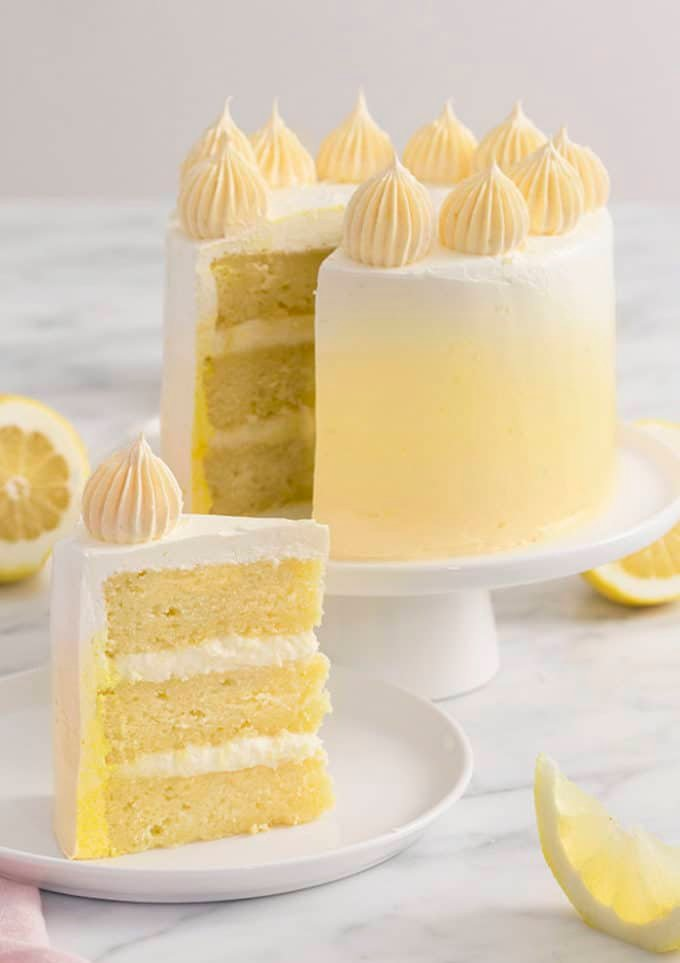 A lemon cake with a yellow ombré that hs a piece on a white plate in the foreground.