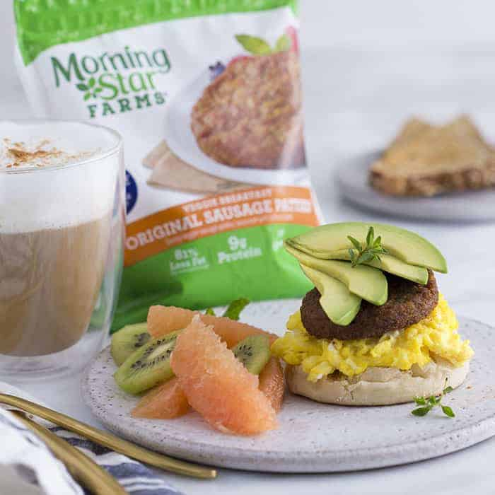 A photo of an english muffin topped with soft scrambled eggs a veggie patty and a fan of avocado