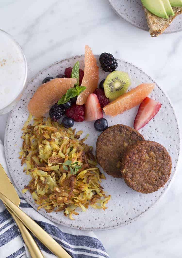 A Top Down photo showing a plate of hash browns, veggie patties and a fruit salad.