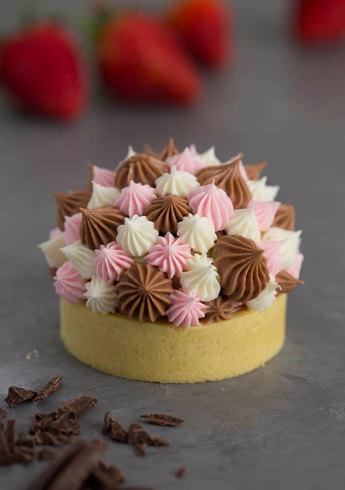 A photo of a Neapolitan tart with different sized dollops of Swiss meringue buttercream piped on top.