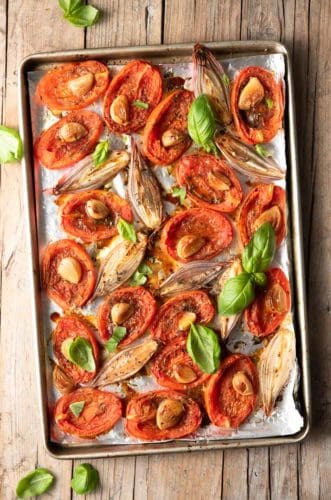 An overhead shot of a baking sheet with oven roasted tomatoes and shallots on it