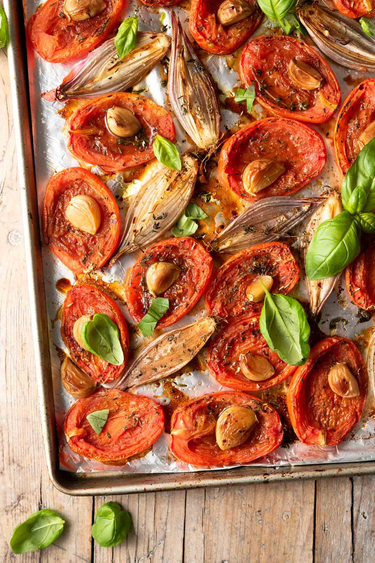 A close up of roasted tomatoes, garlic and shallots on a baking tray