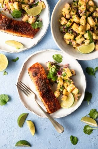 An overhead shot of blackened salmon on a plate with pineapple salsa