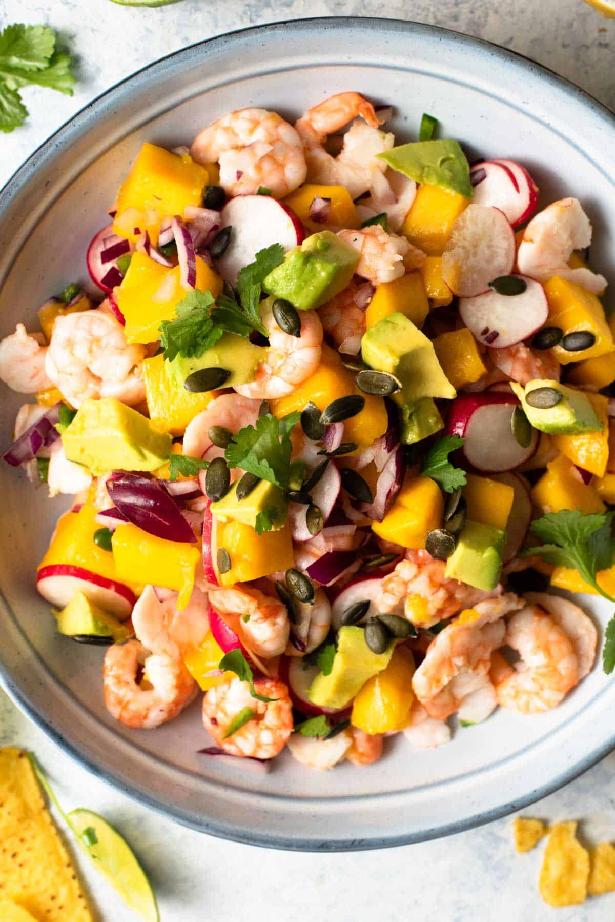 A close up of shrimp, avocado and mango in a bowl with other veggies