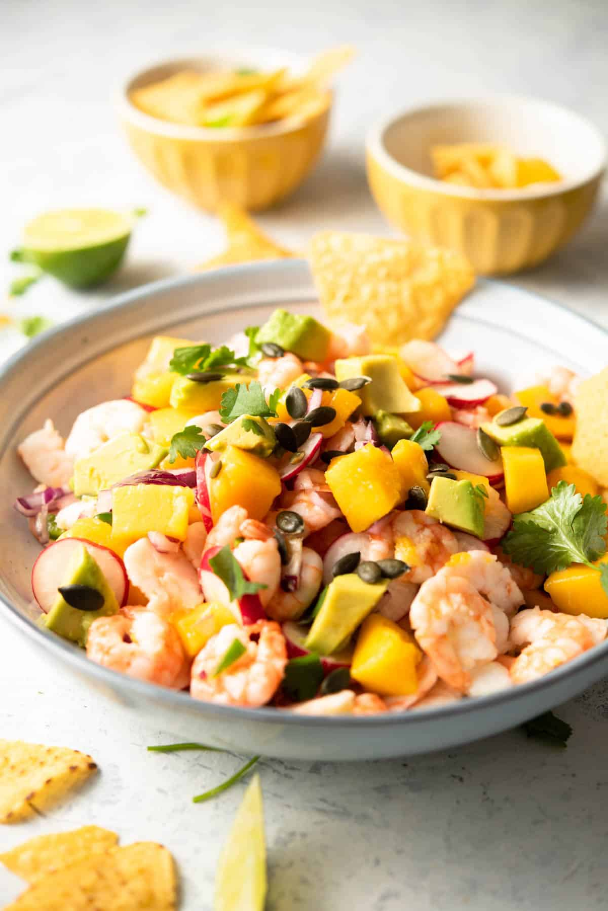 A side shot of shrimp ceviche in a blue bowl with mango and avocado