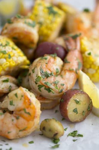 a closeup photo of a shrimp boil with potatoes, corn, and lemon