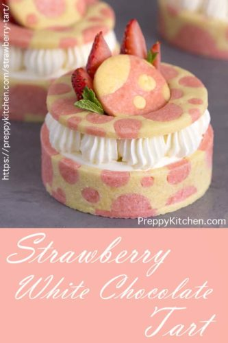 A pinterest image showing pink and white strawberry tarts on a grey surface with text below.
