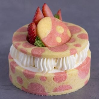 A photo of a strawberry tart with pink dots on the pastry and a strawberry on top.