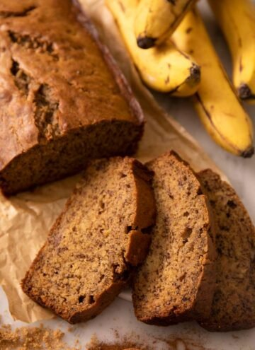 A close up of a loaf of banana bread with some slices cut