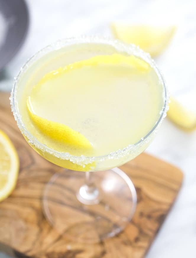A top down shot of a lemon drop cocktail in a coupe glass.