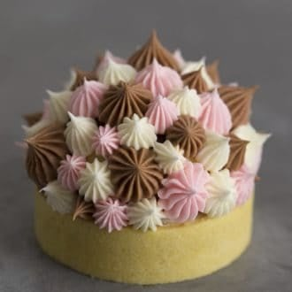 A photo of a Neapolitan tart with Swiss meringue buttercream dollops on top