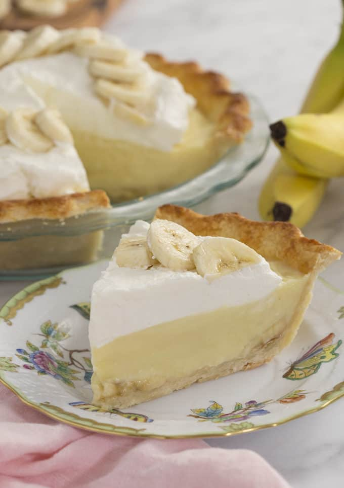 A slice of banana cream pie on a painted porcelain plate