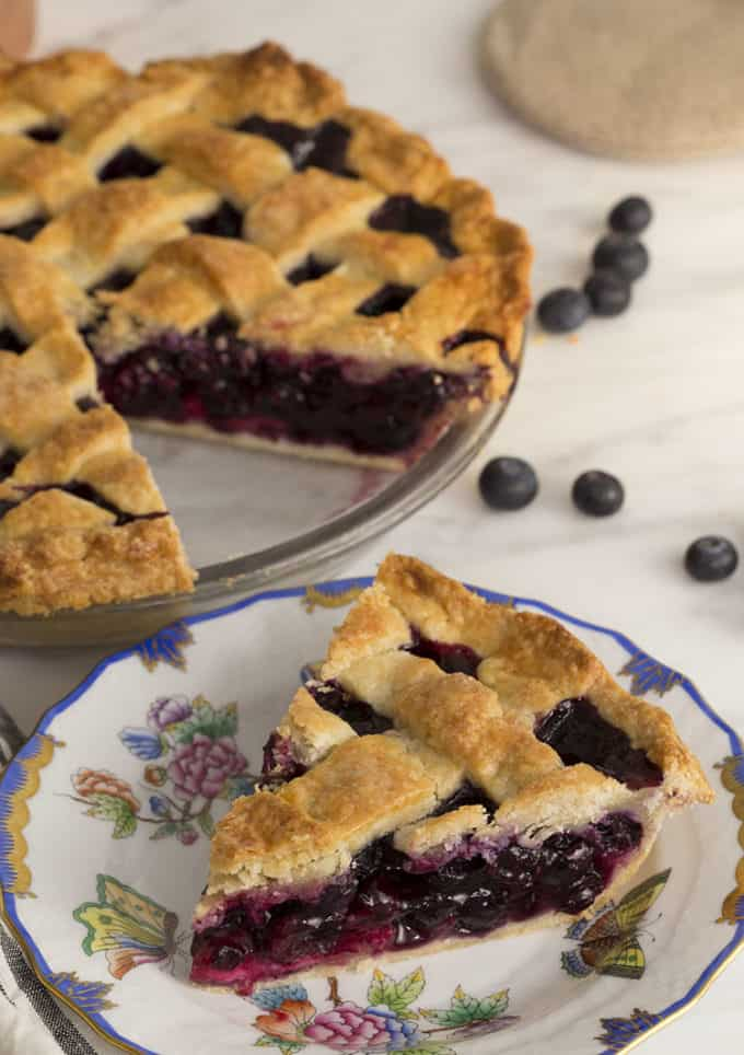 A lattice-topped blueberry pie with a piece cut out in the foreground