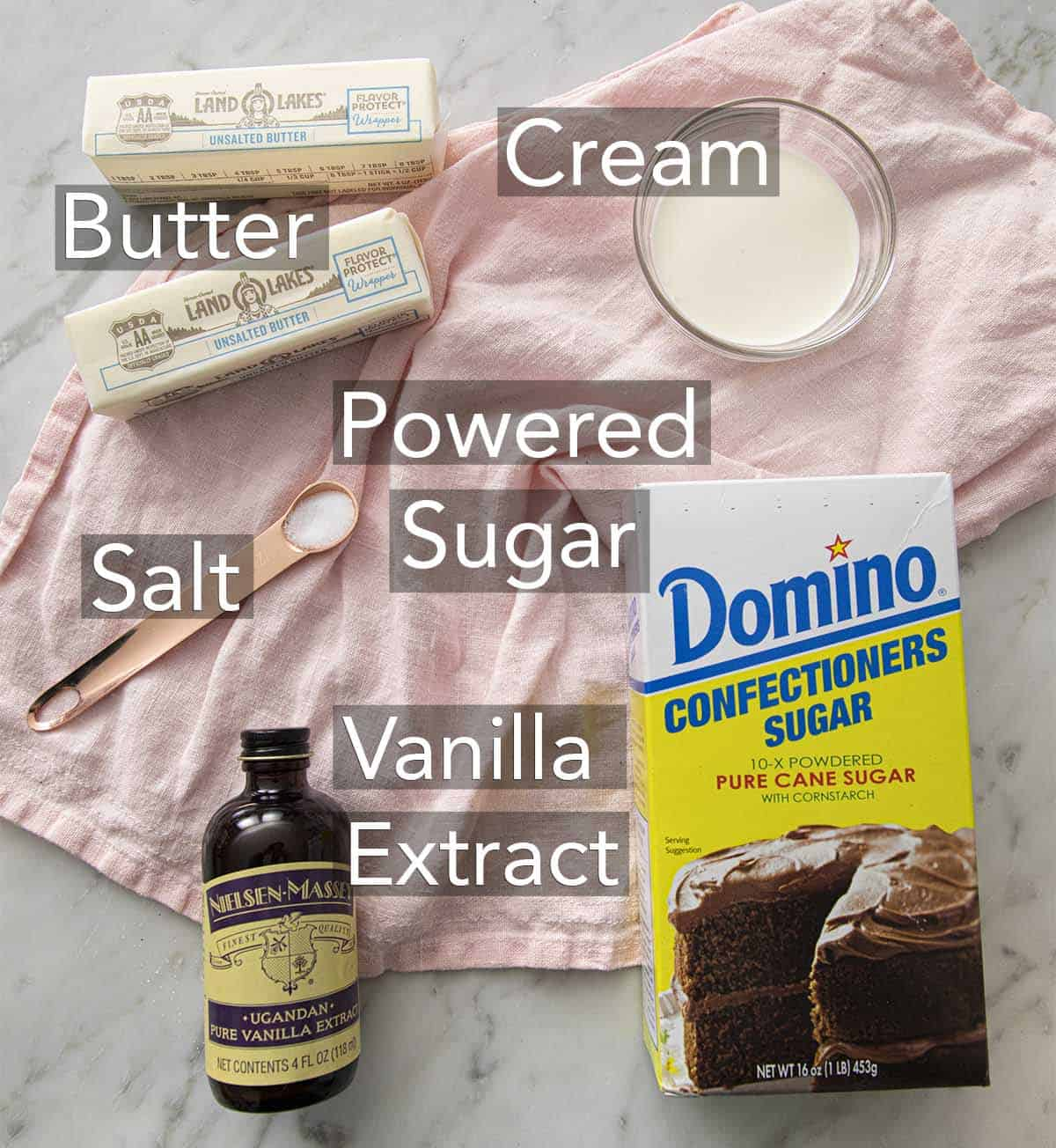 The ingredients for buttercream frosting on a marble surface.