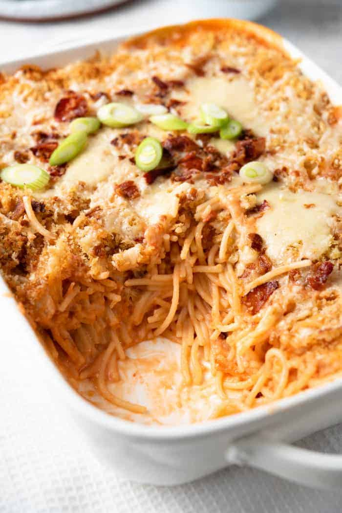 A close up of cheesy chicken spaghetti casserole with a spoonful scooped out
