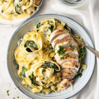 An overhead shot of chicken alfredo with spinach in a blue bowl