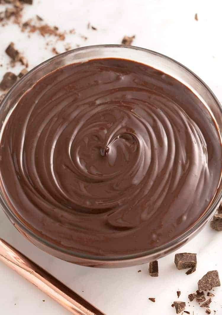 a top down view of a glass bowl filled with chocolate ganache.