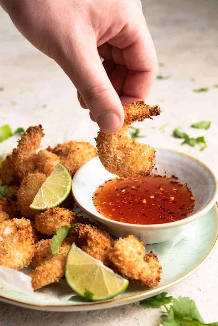 A hand dunking some coconut shrimp into chile dipping sauce