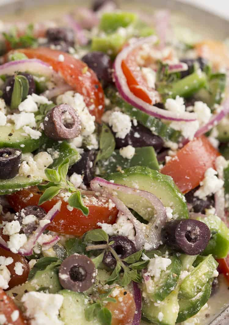 A closeup shot of Greek Salad with tomatoes cucumber and feta.