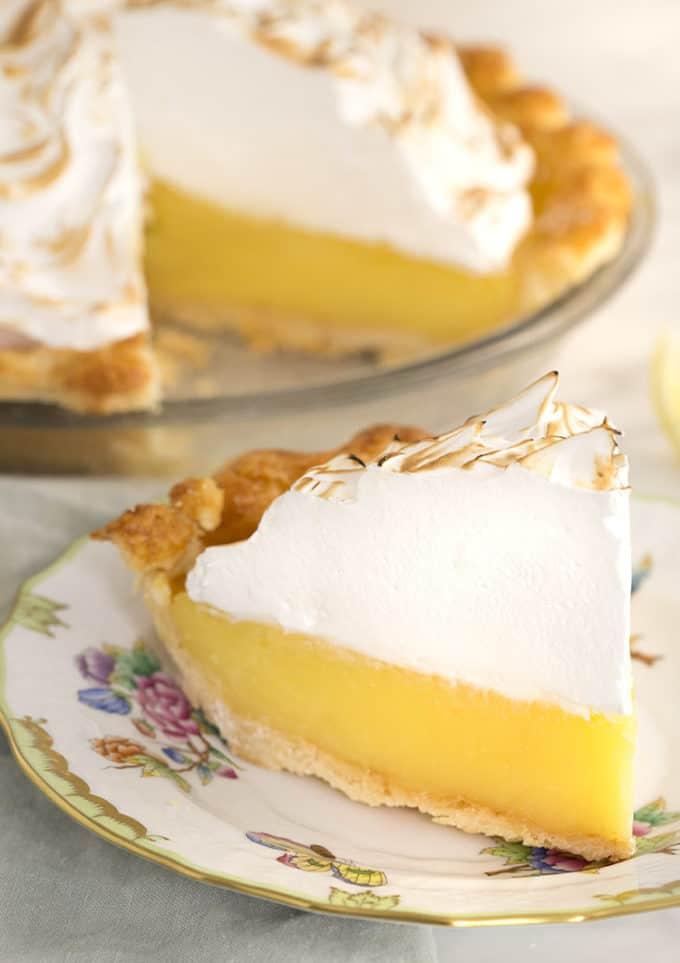 A slice of lemon meringue pie on a porcelain plate.