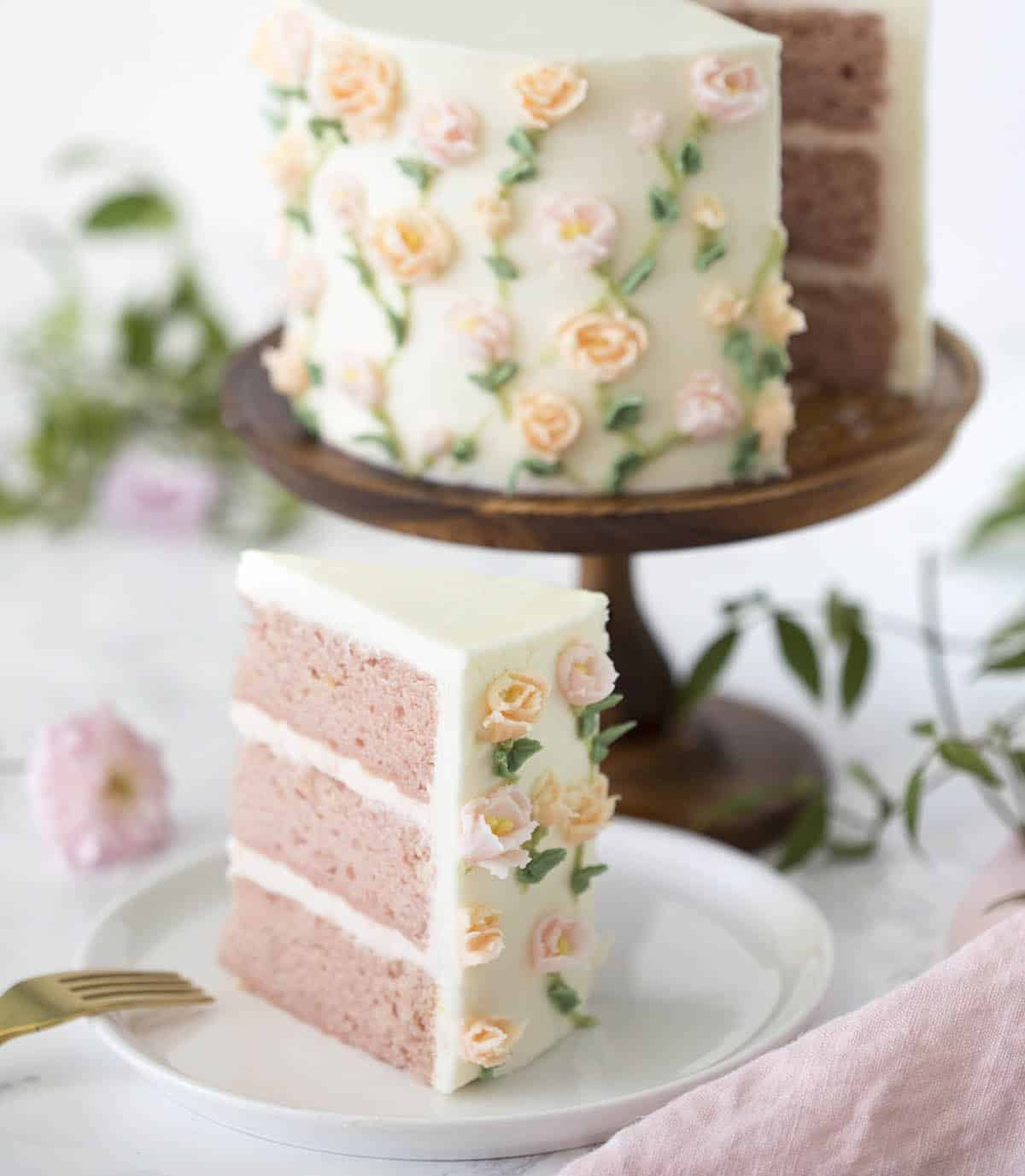 A pink cake with snall roses painted on using buttercream frosting.