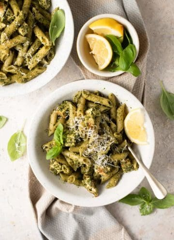 An overhead shot of pesto chicken pasta in two bowls