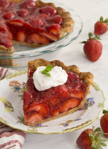 Strawberry pie cut with a piece in the foreground